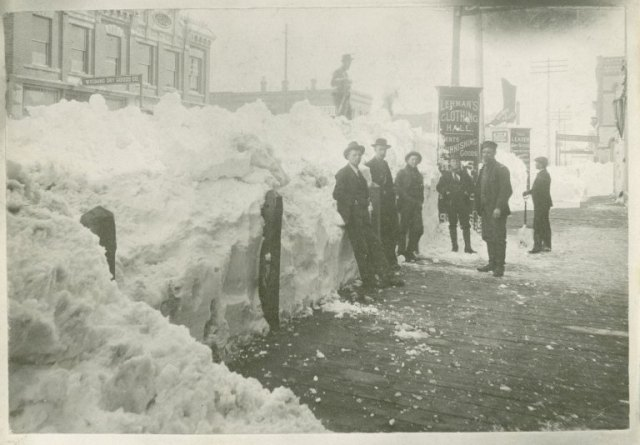 downtown Laramie, Wyoming after the blizzard of 1897. The image shows men standing with snow shovels next to a large drift outside Lehman's Clothing Hall. Photo File: Wyoming - Laramie - Blizzard 1897.