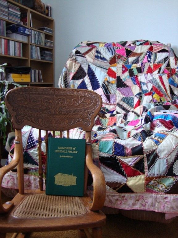 Heckox family crazy quilt and wooden rocking chair, sized for a child.