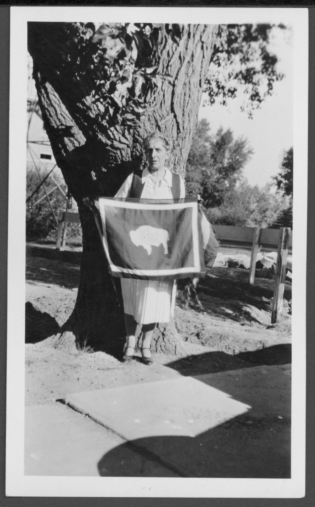 Photograph of Grace Raymond Hebard holding the Wyoming Buffalo Flag, July 10, 1930, University of Wyoming American Heritage Center, Photofile: Hebard, Grace Raymond, Folder 6.