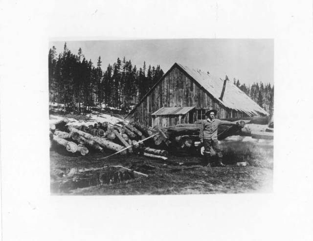 Photo of Hans Kleiber in ranger uniform, standing in front of log cabin with felled trees in the background.