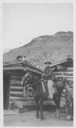 Jacob M. Schwoob riding horseback in front of a log cabin.