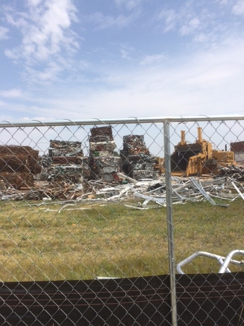 The remaining rubble of the former Laramie High School on August 8, 2017. Photo shows piles of scrap metal in neat piles and a crushing machine behind a chain-link fence.