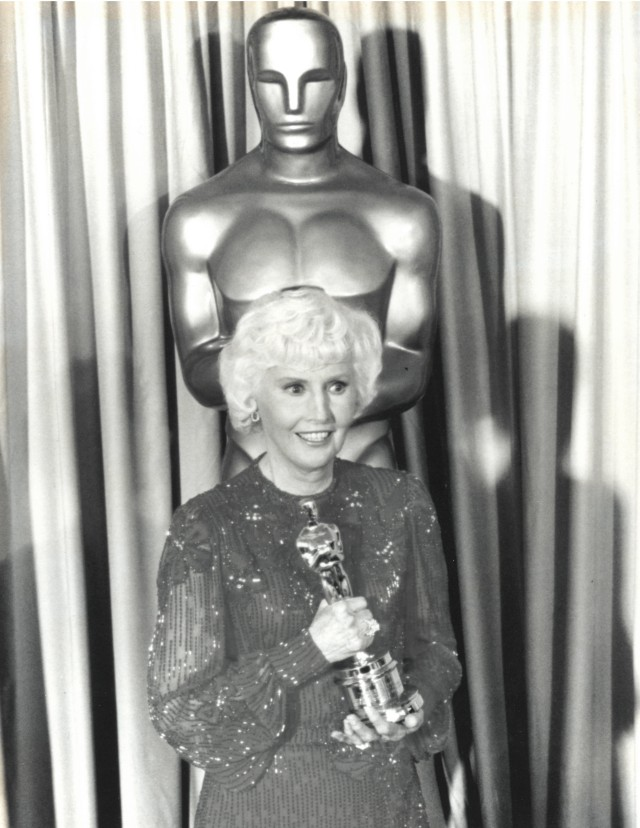 Black and white photo of Barbara Stanwyck holding her Oscar Statue while standing in front of a large Oscar Statue, about 7 feet tall.