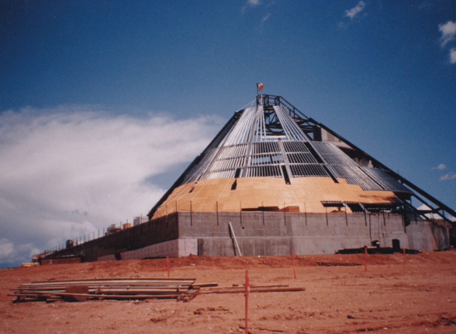 Color photograph of a cone-shaped building being constructed, with U.S. flag mounted on top.