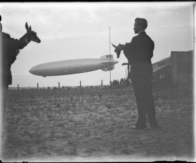 two mean holding pronghorns in the foreground and an airship landing in the background with people watching.